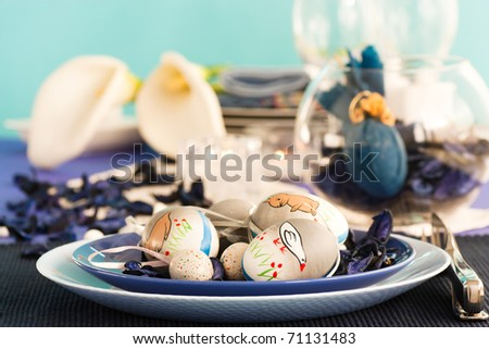 Easter table setting in blue and white tones with candles and flower.