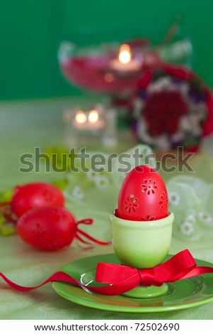 Easter table setting in green and red tones with candles and bouquet.