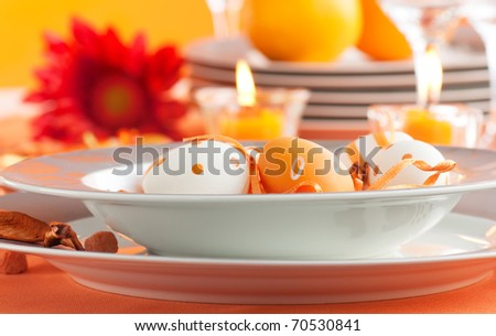 Easter table setting in orange tones with candles and flower.