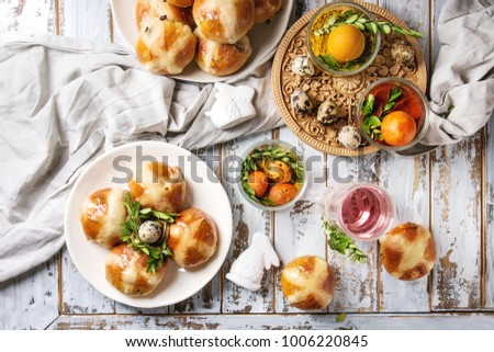 Easter table setting with colored orange eggs, hot cross buns, green branches decorated, empty plate, cutlery, glass of lemonade drink over white plank wooden table with textile tablecloth. Flat lay