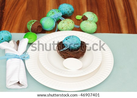 Easter table setting with easter egg and place card. Shallow DOF with chocolate filled eggs in the background.