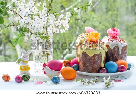 Easter table with Easter cakes and Easter eggs with blossoming Apple tree branch in a vase.