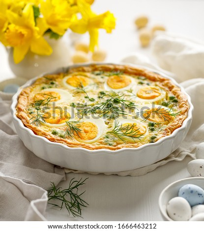 Easter tart quiche with eggs and green peas in casserole dish on a white table