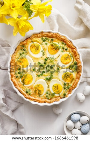 Easter tart quiche with eggs and green peas in casserole dish on a white table, top view