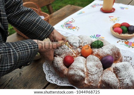 Easter traditions - colorful eggs placed in a traditional sweet bread. #1044968725