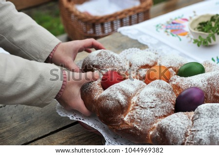 Easter traditions - colorful eggs placed in a traditional sweet bread. #1044969382