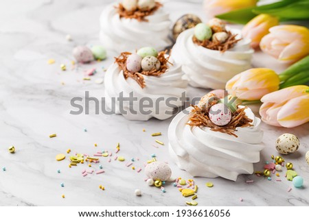 Easter treat - set of white meringues in shape of nest with multicolored candy chocolate eggs, tulips and sprinkles over marble background. Side view, close up, copy space. Holiday symbol ストックフォト ©
