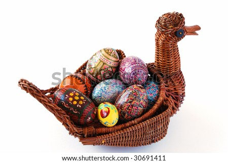 Easter varicolored eggs on a white background.duck wickerwork from willow twigs