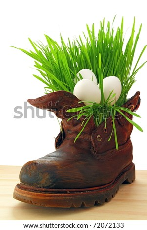 Easter white eggs in old shoes, with fresh grass