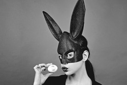 Easter woman. Woman rabbit, easter bunny girl. Red lip imprint on easter egg on red background. Female mouth kiss. Print of red lips on white egg
