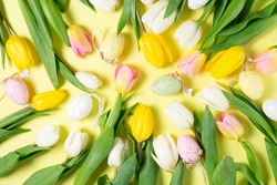 Easter yellow tulips with colored eggs, pattern on yellow background