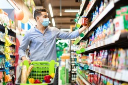Eastern Arabic Guy Buying Food Doing Grocery Shopping Walking With Shop Cart Full Of Groceries In Modern Supermarket, Wearing Face Mask. Male Customer Choosing Staple Products On Shelf In Store