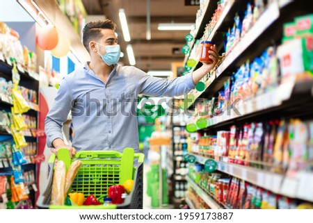 Eastern Arabic Guy Buying Food Doing Grocery Shopping Walking With Shop Cart Full Of Groceries In Modern Supermarket, Wearing Face Mask. Male Customer Choosing Staple Products On Shelf In Store Stockfoto ©