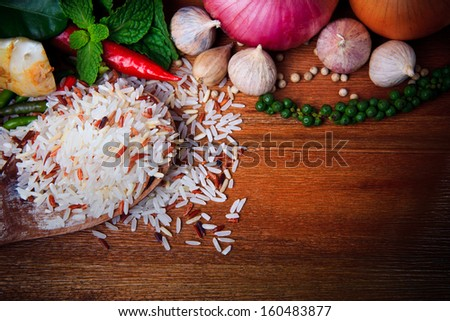 eastern food spice herb rice garlic chilly pepper mint leaves red onion green pepper on wood table background