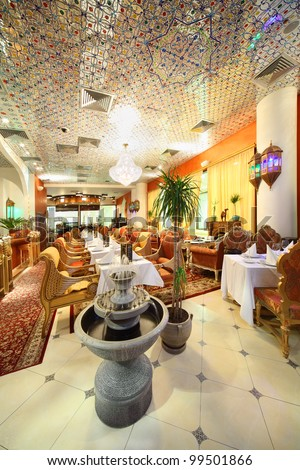 eastern interior of beautiful restaurant, potted palms and fountain - stock photo