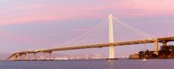 Eastern span of San-Francisco-Oakland Bay Bridge panoramic view at Twilight. Shot from Treasure Island, San Francisco, California, USA.