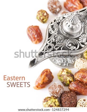 Eastern sweet (still life with nuts, candy, metal vase and date isolated on white background)