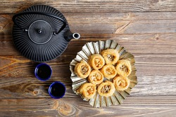 Eastern sweets baklava, teapot and two small bowls on wooden table. Top view.