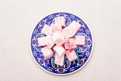 Eastern sweets. Traditional Turkish delight Rahat lukum with a rose on ceramics with typical folk patterns. Stone background, copy space, top view