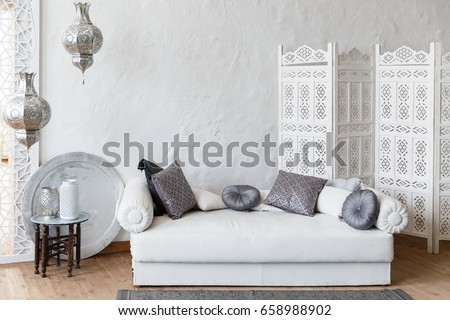 Eastern traditional interior. Morocco style room. Arch and window with beautiful carving. White and gray room with beautiful white sofa and pillows #658988902