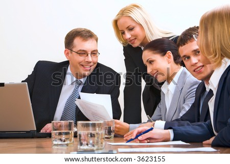 Easy going discussing business questions people sitting around the table with an opened laptop, documents and glasses on it - stock photo
