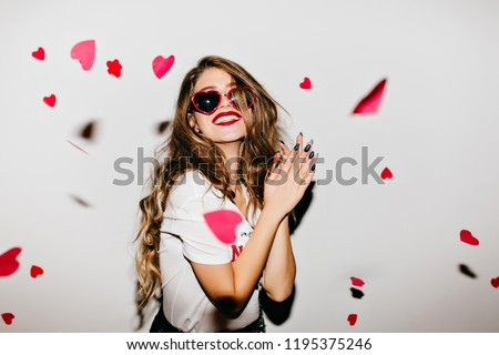 Easy-going girl with long hair expressing positive emotions in valentine\'s day. Excited lady looking at fallen paper hearts and laughing.