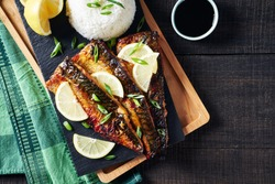 Easy grilled mackerel or saba shioyaki fish with golden crispy skin- japanese dish served with rice, soya sauce, lemon, chive on a black cutting board on a dark wooden table, top view, copy space