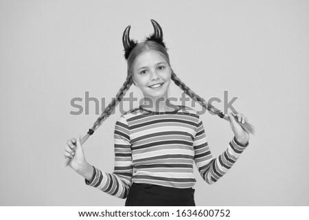 Easy holiday hairdo for long length hair. Halloween child hold long plait hairdo. Small girl wear red devil horns headband with braid hairdo. Hairdo salon. Beauty and hair parlor.