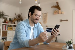 Easy paying. Happy millennial man use debit plastic card mobile telephone to provide loan mortgage payment online. Young male loyal bank client refill balance receive cash reward on electronic wallet