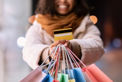 Easy Payment Concept. Closeup Of Unrecognizable Black Woman In Winter Coat Showing Credit Card, Holding Bright Colorful Shopping Bags From Mall, Standing Outdoors In The Evening. Selective Focus