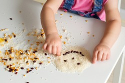 Easy sensory activities for babies toddler, preschoolers. Little girl hands playing with rice, popcorn, beans, pasta. Sensory play at home, games for sensory processing disorder, activities Montessori