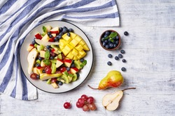 Easy summer fruit salad on a plate of mango, blueberries, red grape, pears, apple, with fresh mint, on a white wooden table, horizontal view, copy space