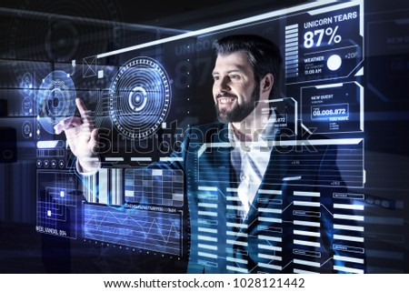 Easy usage. Enthusiastic elegant optimistic programmer feeling glad and smiling while standing in front of a futuristic screen and working with convenient modern technologies