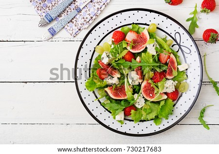 """Easy vegetarian salad with figs, strawberries, grapes, blue cheese """"Dorblu"""" and lettuce. Flat lay. Top view"""