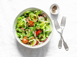 Easy vegetarian vegetable salad with fresh vegetables. Cherry tomatoes , romano lettuce, cucumbers, radishes and french mustard, olive oil, lemon salad dressing on a light background, top view