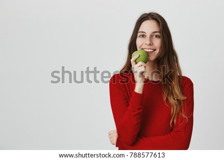 Stock Photo Eat apple per day. Healthy lifestyle concept. Close up isolated portrait of good-looking dark haired girl in red sweater smiling wit teeth, holding fruit in front of mouth, feeling happy and relaxed.