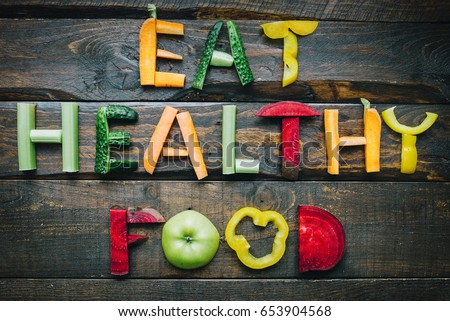 Shutterstock Eat healthy food fresh vegetables flat lay lettering on dark wooden table top view. Nutrition organic meal ingredients concept. Nice cooking postcard, poster, banner.