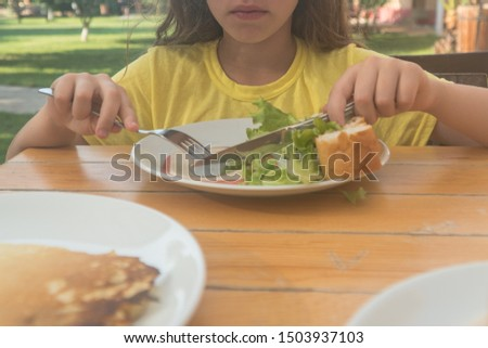 eat on the street. child eats in a cafe.