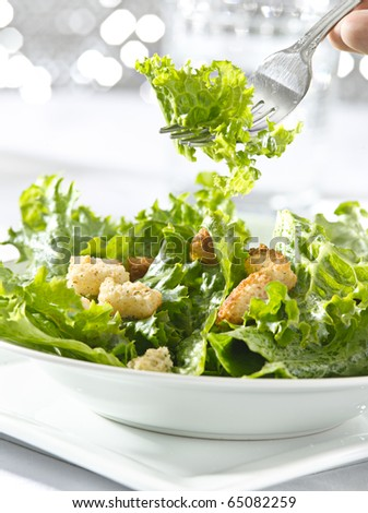 eating a leafy green salad with fork