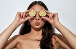 Eating for Healthy Skin. Young playful woman with pout lips covering her eyes with two halves of green lime while standing on light background in studio. Nutrition and natural beauty concept
