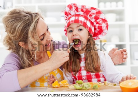 Eating fresh fruits is healthy - woman and little girl in the kitchen