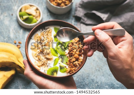 Eating healthy breakfast yogurt bowl with granola and fruits kiwi, banana, coconut. Male hands holding coconut bowl with yogurt and fruits