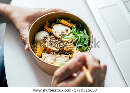 Eating healthy lunch bowl in man's hands. Delicious balanced food concept. Felivery food, home office, dieting, detox, vegetarian food concept