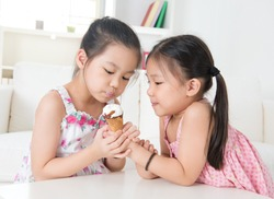 Eating ice cream cone. Asian children sharing an ice cream. Beautiful girls model at home.