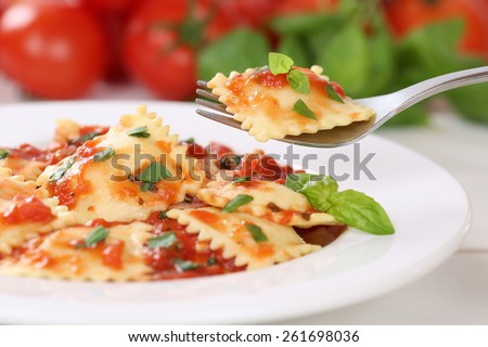 Eating Italian Pasta Ravioli with tomato sauce noodles meal with basil on a plate