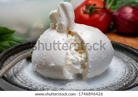 Eating of fresh handmade soft Italian cheese from Puglia, white balls of burrata or burratina cheese made from mozzarella and cream filling close up Сток-фото ©
