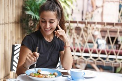 Eating out, lifestyle and travelling concept. Portrait of pretty european woman eating at restaurant table healthy food, drinking coffee, dining alone, smiling, tourist at cafe of her hotel