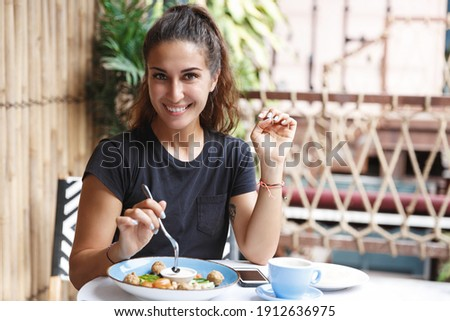 Eating out, lifestyle and travelling concept. Portrait of pretty european woman eating at restaurant table healthy food, drinking coffee, dining alone, smiling, tourist at cafe of her hotel.