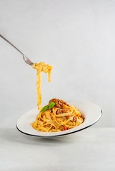 Eating pasta. Egg pasta tagliatelle with bolognese sauce made from meat and tomato sauce. Traditional italian dish from Bologna. Dynamic photo. Minimalism. Light grey background. Copy space.
