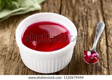 Eating red jelly or jello, spoonful of jelly on the side (Selective Focus, Focus in the middle of the image)
